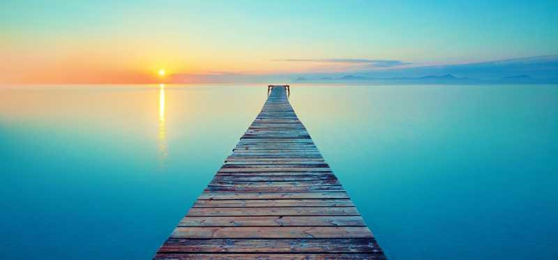 Serene image of a wooden dock going out into the ocean at sunset.