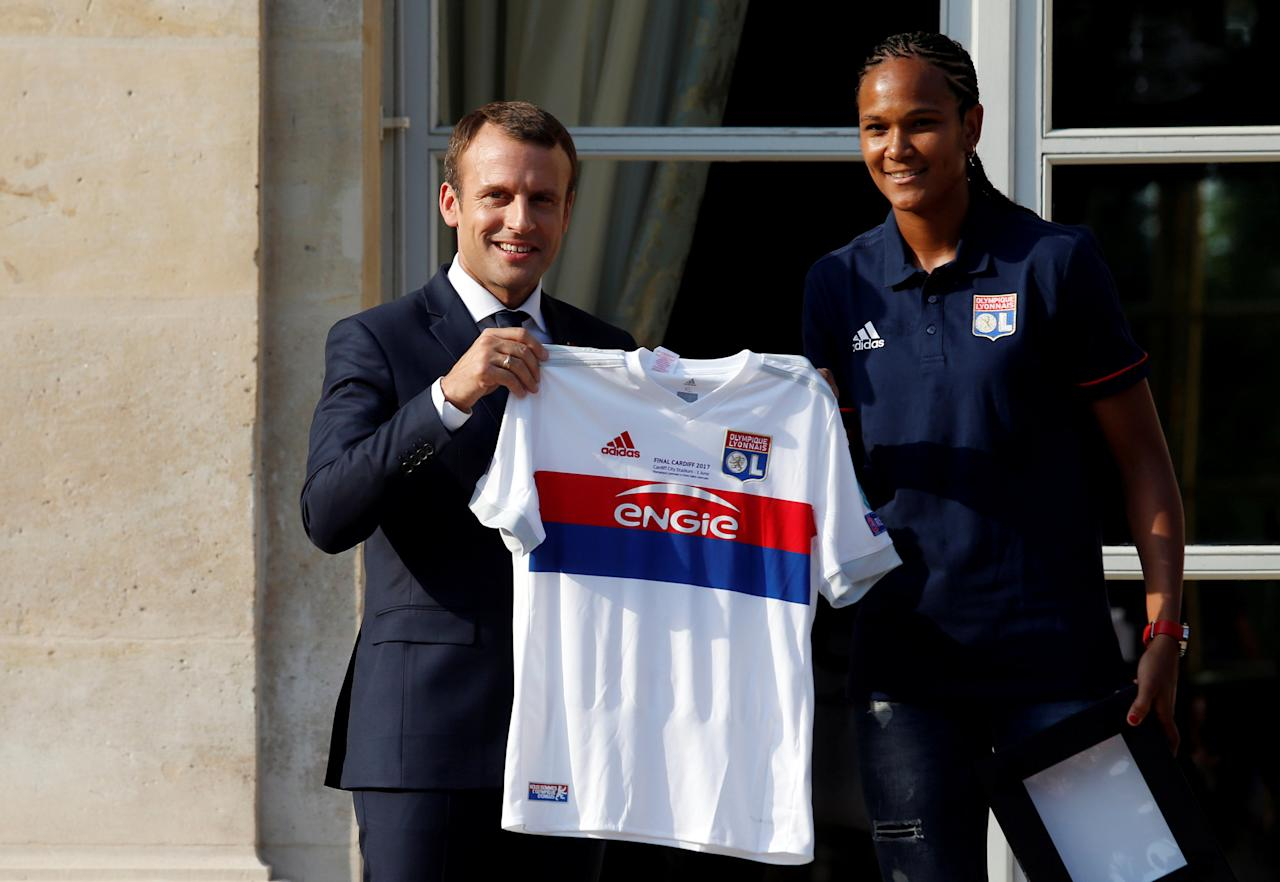French President Emmanuel Macron (L) poses after he received a jersey from Lyon's soccer captain Wendie Renard (R) during a ceremony at the Elysee Palace in Paris, France, June 20, 2017 to celebrate the victory of Lyon during the UEFA Women's Champions League.    REUTERS/Geoffroy van der Hasselt/Pool