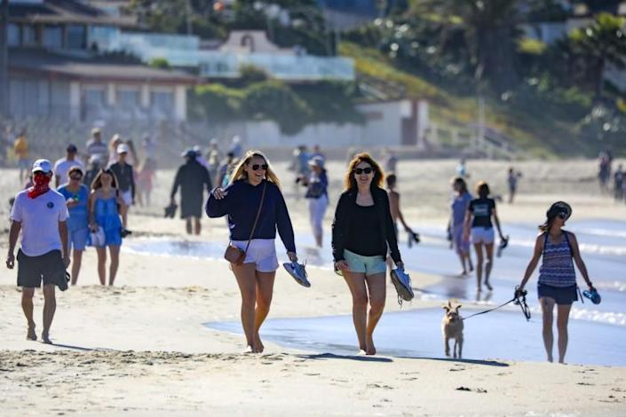 """LAGUNA BEACH, CA - MAY 05: People stroll along Laguna Beach on Tuesday morning as city with State's blessings reopened its beaches for active use only. The first phase of the reopening includes 6-10 a.m. hours Mondays through Fridays. in Laguna Beach on Tuesday, May 5, 2020 in Laguna Beach, CA. (Irfan Khan / Los Angeles Times) <span class=""""copyright"""">(Irfan Khan/Irfan Khan/Los Angeles Times)</span>"""