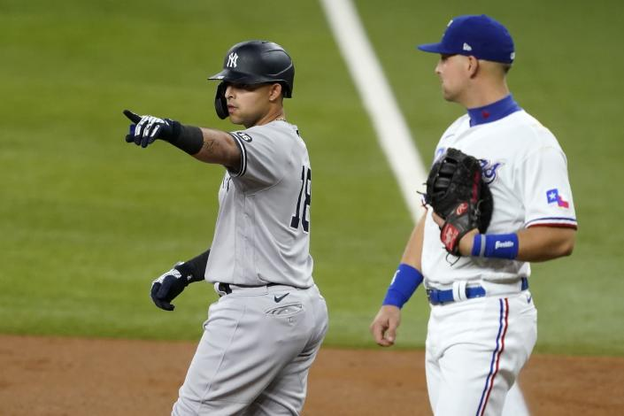 New York Yankees' Rougned Odor points to the dugout after hitting a single as Texas Rangers first baseman Nate Lowe stands by the base in the second inning of a baseball game in Arlington, Texas, Tuesday, May 18, 2021. (AP Photo/Tony Gutierrez)