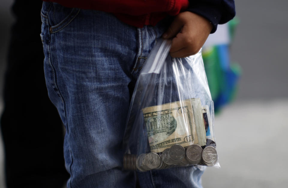 A boy carries cash to visit his mother at California Institute for Women state prison in Chino, California May 5, 2012. An annual Mother's Day event, Get On The Bus, brings children in California to visit their mothers in prison. Sixty percent of parents in state prison report being held over 100 miles (161 km) from their children.  Picture taken May 5, 2012   REUTERS/Lucy Nicholson (UNITED STATES - Tags: CRIME LAW SOCIETY)  ATTENTION EDITORS PICTURE 09 OF 28 FOR PACKAGE 'MOTHER'S DAY BEHIND BARS'