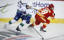 Vancouver Canucks' Quinn Hughes, left, watches as Calgary Flames' Andrew Mangiapane gets away from him during third-period NHL hockey game action in Calgary, Alberta, Monday, Jan. 18, 2021. (Jeff McIntosh/The Canadian Press via AP)