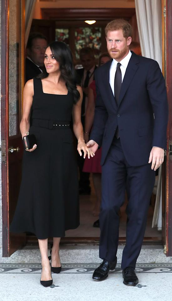 <p>For a summer garden party at Glencairn House on 10 July, the Duchess of Sussex changed into her third outfit of the day. In a surprising sartorial move, the royal opted for a belted dress by Emilia Wickstead and accessorised the look with a Givenchy clutch, Birks earrings and a pair of Aquazurra heels. <em>[Photo: PA]</em> </p>