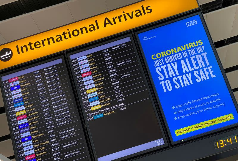 FILE PHOTO: A public health campaign message is displayed on an arrivals information board at Heathrow Airport, following the outbreak of the coronavirus disease (COVID-19), London, Britain