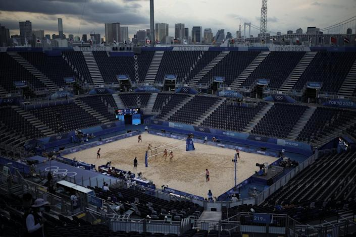 Players compete in a volleyball match in a nearly empty venue.