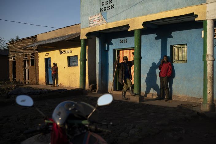 Residents stand outside buildings as the sun rises in Kinigi, Rwanda. In 2005, the government adopted a model to steer 5% of tourism revenue from Volcanoes National Park to build infrastructure in surrounding villages, including schools and health clinics. Two years ago, the share was raised to 10%. (Photo: Felipe Dana/AP)