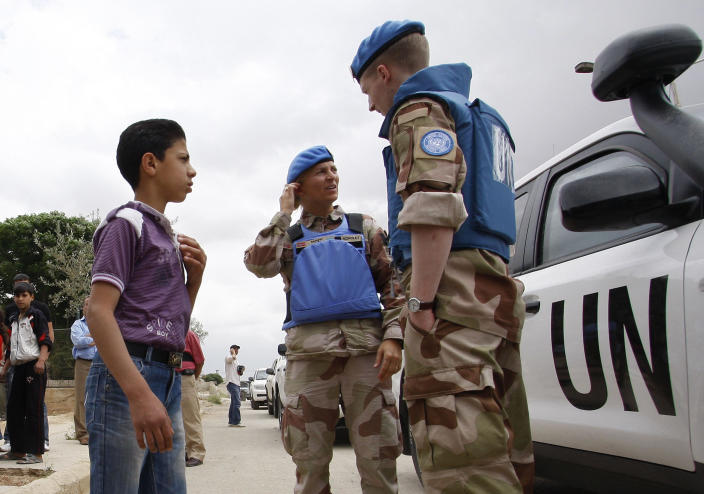 In this picture taken during a UN observer-organized media tour, a Syrian boy talks with UN observers during their visit to Hama city, central Syria, on Thursday May 3, 2012. Syrian security forces stormed dorms at a northwestern university to break up anti-government protests there, killing at least four students and wounding several others with tear gas and live ammunition, activists and opposition groups said Thursday. (AP Photo/Muzaffar Salman)