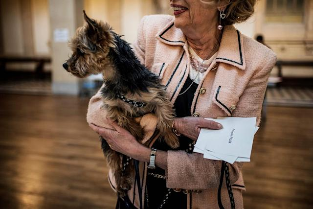 <p>A woman carries her dog as she cast her ballot at a polling station in Lyon, on April 23, 2017, during the first round of the Presidential elections. (Photo: Jeff Pachoud/AFP/Getty Images) </p>
