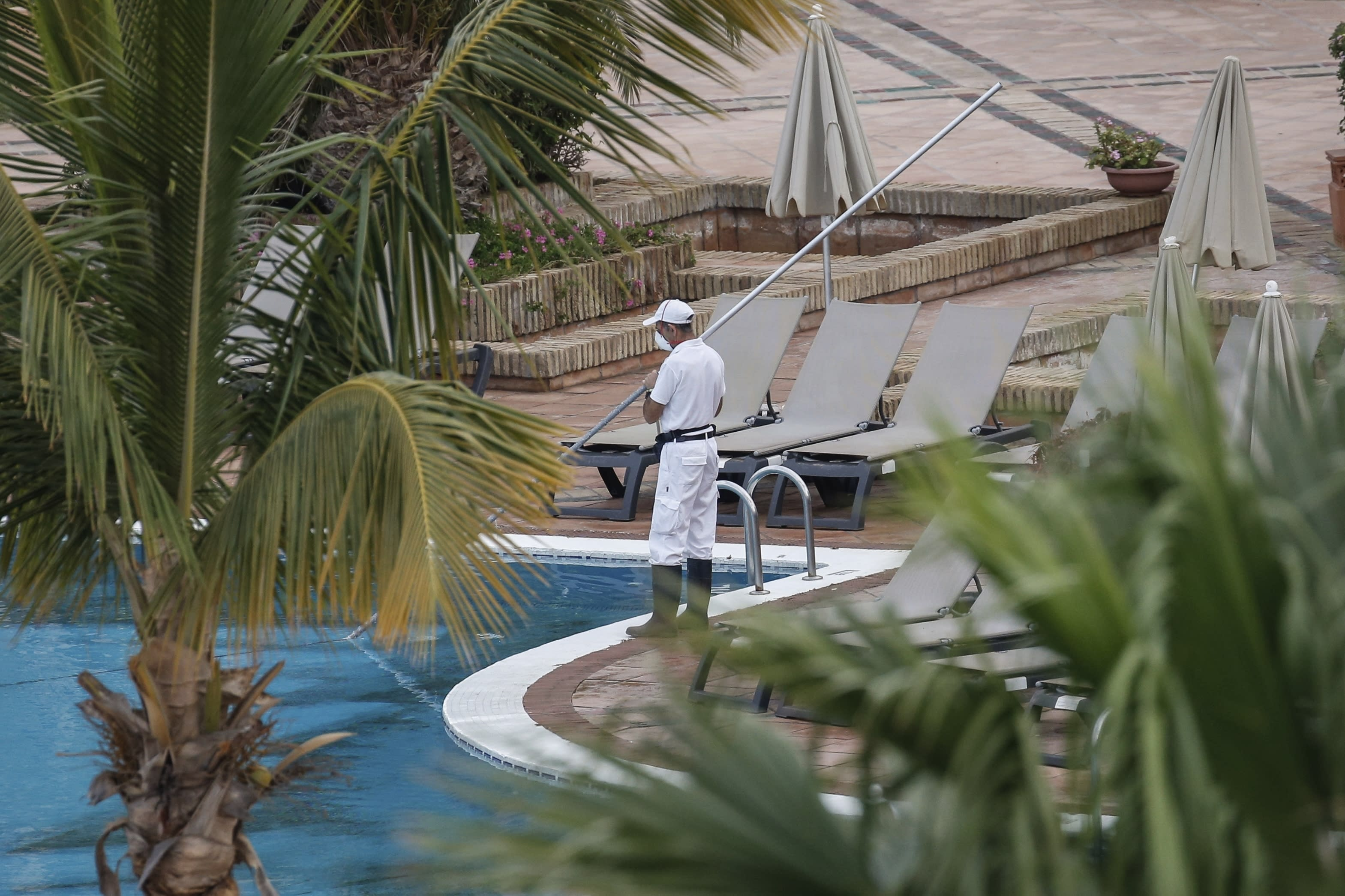 A staffer cleans the swimming pool of the H10 Costa Adeje Palace hotel in La Caleta, in the Canary Island of Tenerife, Spain, Thursday, Feb. 27, 2020. Spanish officials say a tourist hotel on the Canary Island of Tenerife has been placed in quarantine after an Italian doctor staying there tested positive for the COVID-19 virus and Spanish news media says some 1,000 tourists staying at the complex are not allowed to leave. (AP Photo/Joan Mateu)