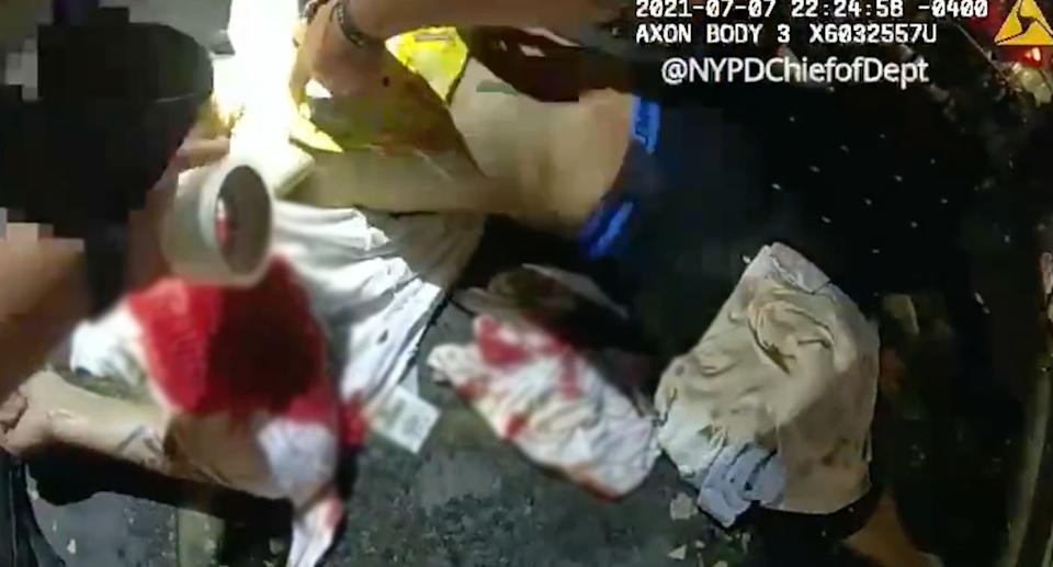 The police officer tapes the chip bag to the man's chest.