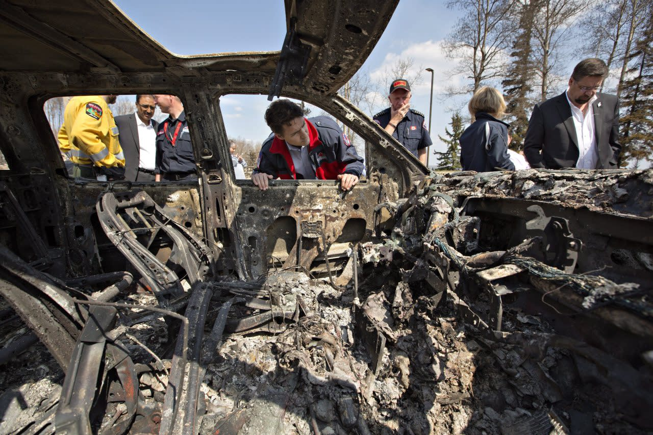 Prime Minister Justin Trudeau, centre left, and Fort McMurray Fire Chief Darby Allen, centre right, look over a burnt out car during a visit to Fort McMurray, Alta., on Friday, May 13, 2016. THE CANADIAN PRESS/Jason Franson
