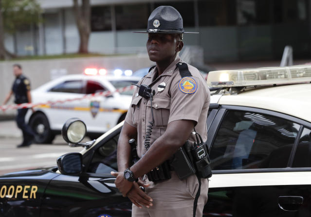 <p>A Florida Highway patrolman stands by his car blocking the entrance to a street near the scene of a mass shooting at Jacksonville Landing in Jacksonville, Fla., Aug. 26, 2018. Florida authorities are reporting multiple fatalities at the riverfront mall that was hosting a video game tournament. (Photo: John Raoux/AP) </p>