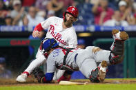 Philadelphia Phillies' Bryce Harper, left, scores past Chicago Cubs catcher Willson Contreras on a RBI-single by Didi Gregorius during the sixth inning of a baseball game, Tuesday, Sept. 14, 2021, in Philadelphia. (AP Photo/Matt Slocum)