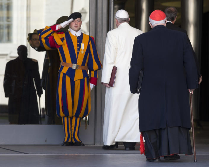 """A Vatican Swiss Guard salutes as Pope Francis arrives to open the morning session of an extraordinary consistory in the Synod hall at the Vatican City, Friday, Feb. 21, 2014. Pope Francis is leading a two-day meeting urging his cardinals to find """"intelligent, courageous"""" ways to help families under threat today without delving into case-by-case options to get around Catholic doctrine. He said the church must find ways to help families with pastoral care that is """"full of love.""""(AP Photo/Alessandra Tarantino)"""