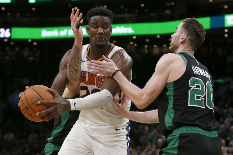 Phoenix Suns center Deandre Ayton, center, is fouled by Boston Celtics forward Gordon Hayward, right, during the second half of an NBA basketball game, Saturday, Jan. 18, 2020, in Boston. (AP Photo/Mary Schwalm)