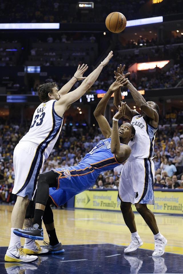 Oklahoma City Thunder forward Kevin Durant, center, shoots as he falls back between Memphis Grizzlies center Marc Gasol (33) and Tony Allen in the second half of Game 6 of an opening-round NBA basketball playoff series Thursday, May 1, 2014, in Memphis, Tenn. Durant led Oklahoma City with 36 points as they won 104-84 to even the series 3-3. (AP Photo/Mark Humphrey)