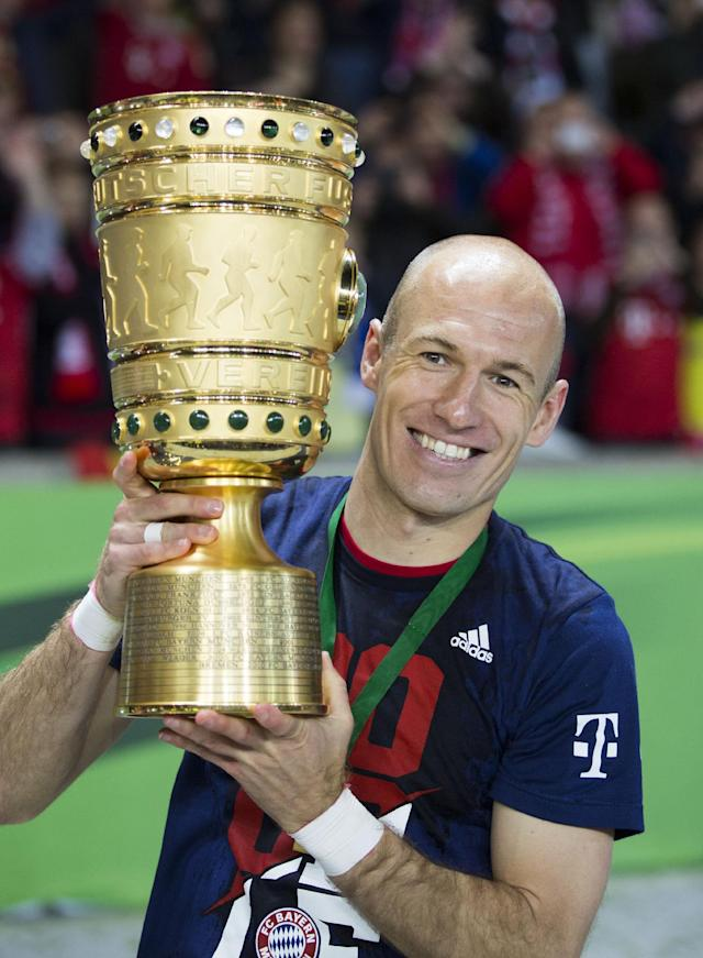 Bayern's Arjen Robben of the Netherlands holds the trophy after winning the German Soccer Cup Final between FC Bayern Munich and Borussia Dortmund at the Olympic Stadium in Berlin, Germany, Saturday, May 17, 2014. (AP Photo/Gero Breloer)