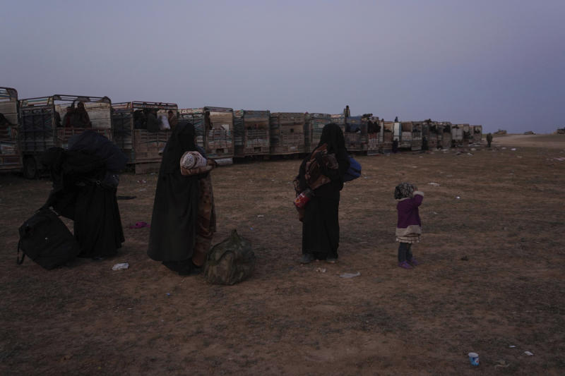 Women and children stand near trucks after being evacuated out of the last territory held by Islamic State militants, outside Baghouz, Syria, Monday, March 4, 2019. Hundreds of people including IS fighters evacuated their last foothold in eastern Syria hours after U.S.-backed Syrian fighters said they were forced to slow their advance because the extremists are using civilians as human shields.(AP Photo/Andrea Rosa)