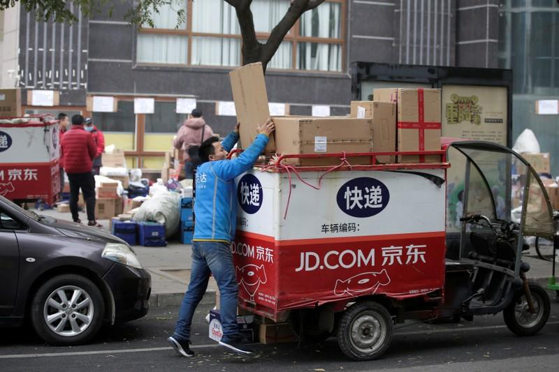 FILE PHOTO: A deliveryman packs parcels on the top of a tricycle after the 11.11 Singles' Day shopping festival in Beijing