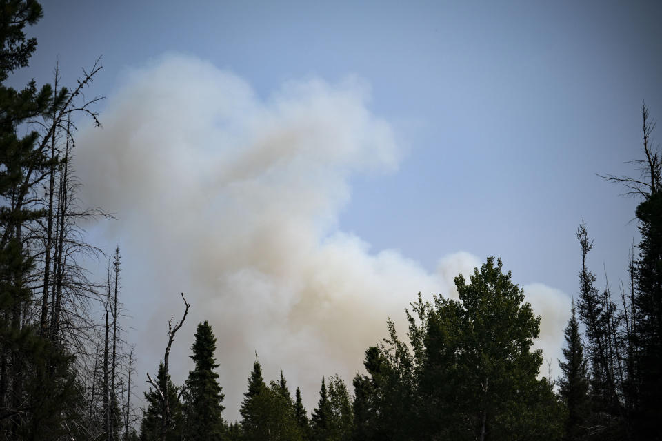 Smoke rises above the Superior National Forest as the Greenwood Fire burns through towards Highway 2 towards the northeast on Monday, Aug. 16, 2021, in Duluth, Minn. The wildfire has continued to grow and spread towards the northeast as firefighters battle the flames from both the ground and air. (Alex Kormann/Star Tribune via AP)