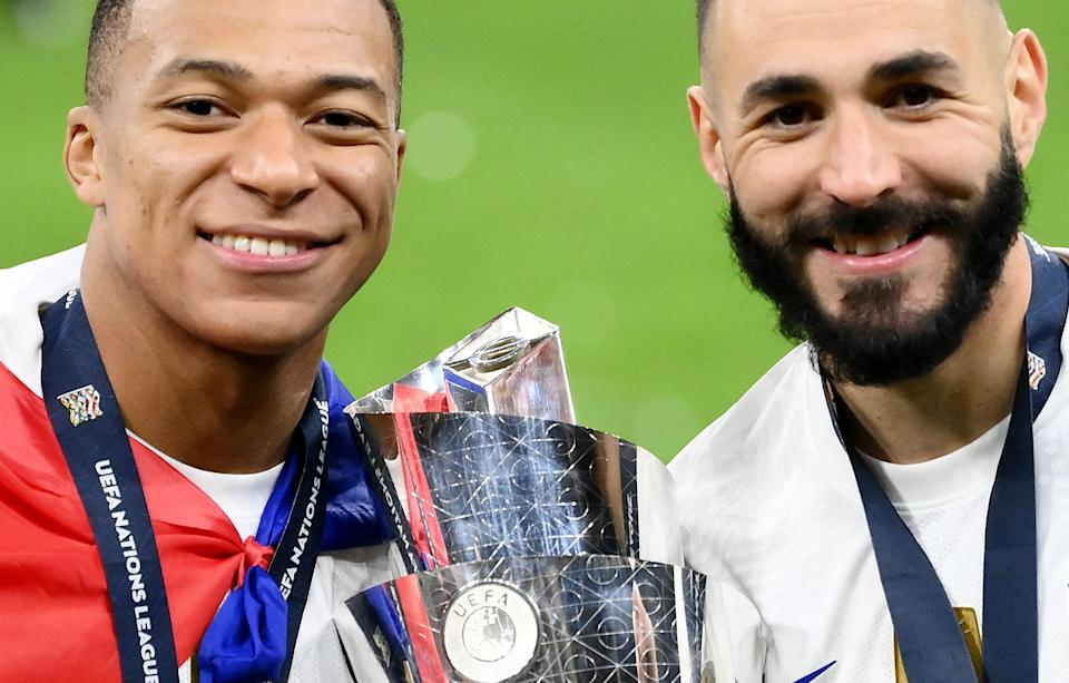 France's forward Kylian Mbappe (L) and France's forward Karim Benzema pose with the trophy at the end of the Nations League final football match between Spain and France at San Siro stadium in Milan, on October 10, 2021. (Photo by FRANCK FIFE / AFP) (Photo by FRANCK FIFE/AFP via Getty Images)