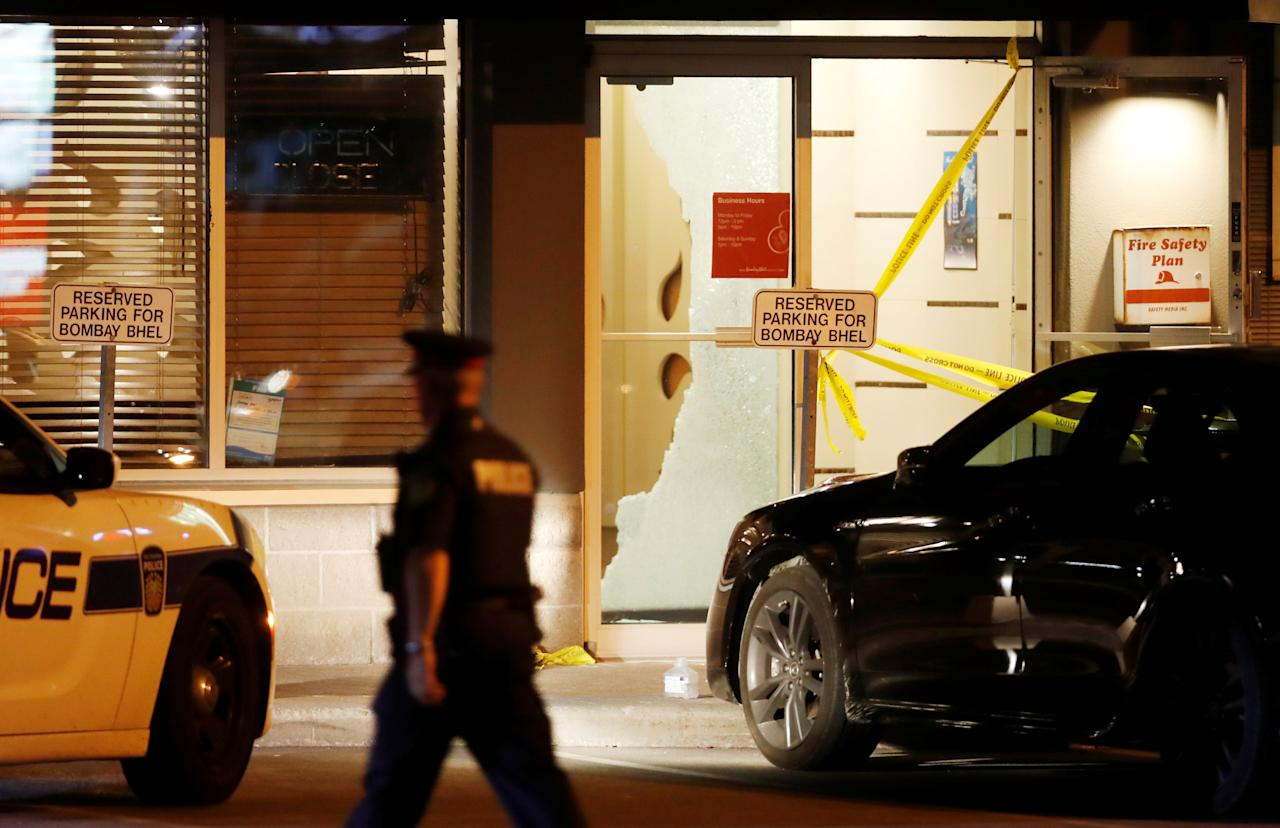<p>A police officer walks in front of shattered glass at Bombay Bhel restaurant, where two unidentified men set off a bomb on May 24, wounding more than a dozen people, in Mississauga, Ont. (Photo from Reuters/Mark Blinch) </p>