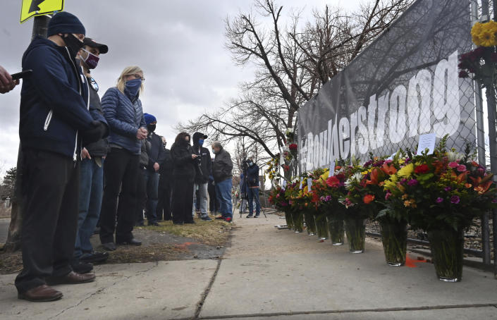 A solemn group of King Soopers employees, left, some from the Boulder store and some from the same district, brought large displays of flowers for each of the victims of a mass shooting at a Boulder Kings Soopers store on Monday. Each display had a card with condolences for the victims' families and signed by their King Sooper family. The group brought their flowers to a fence around the King Soopers where a makeshift memorial has been made for the victims of a mass shooting, Tuesday, March 23, 2021. (Jerilee Bennett/The Gazette via AP)