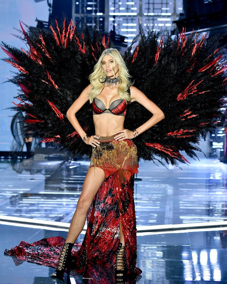 <p>Devon Windsor took to the runway in a red asymmetric skirt with co-ordinating wings. <em>[Photo: Getty]</em> </p>
