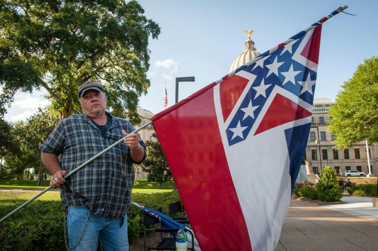 A protestor rolls up the Mississippi flag after the state legislature voted to change it, outside the state capitol building in Jackson, Mississippi on June 28, 2020 (AFP Photo/Rory Doyle)