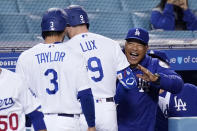 Los Angeles Dodgers manager Dave Roberts, right, congratulates Gavin Lux, center, and Chris Taylor after Lux hit a three-run home run during the eighth inning of an interleague baseball game against the Seattle Mariners Tuesday, May 11, 2021, in Los Angeles. (AP Photo/Mark J. Terrill)