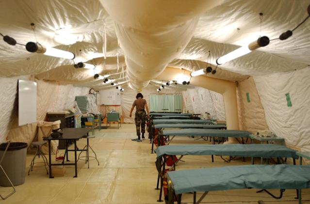 400707 05: A U.S. soldier cleans the floor of a field hospital ward for Al Qaeda and Taliban detainees at Camp X-Ray February 7, 2002 in Guantanamo Bay, Cuba. Dozens of prisoners have been treated at the field hospital, some for pre-existing conditions. An amputation took place February 7. (Photo by Chris Hondros/Getty Images)