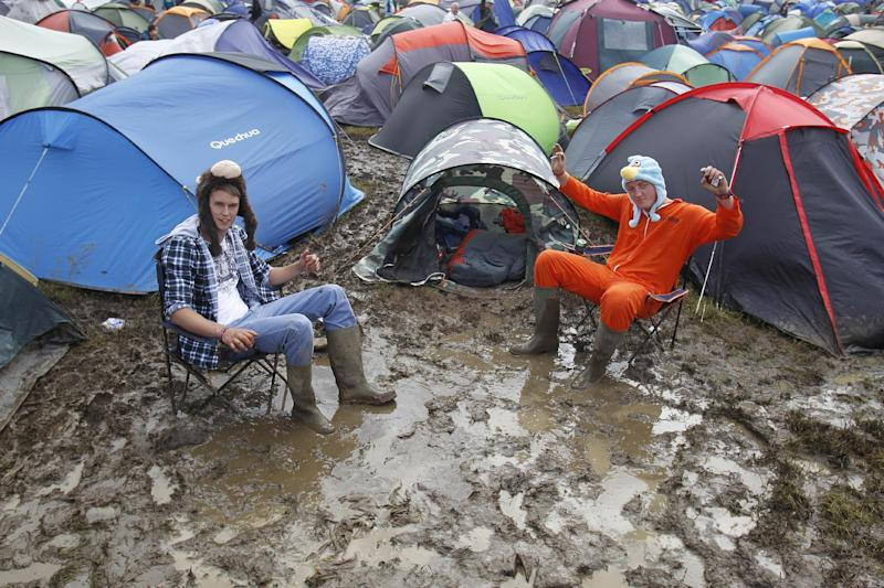 Festival goers sits amongst the mud at the campsite at the Isle of Wight festival on the Isle of Wight england Friday June 22, 2012. Hundreds of music fans have been stranded in their cars overnight after rainstorms caused chaos on travel routes to the Isle of Wight Festival. (AP Photo/Peter Byrne/PA) UNITED KINGDOM OUT