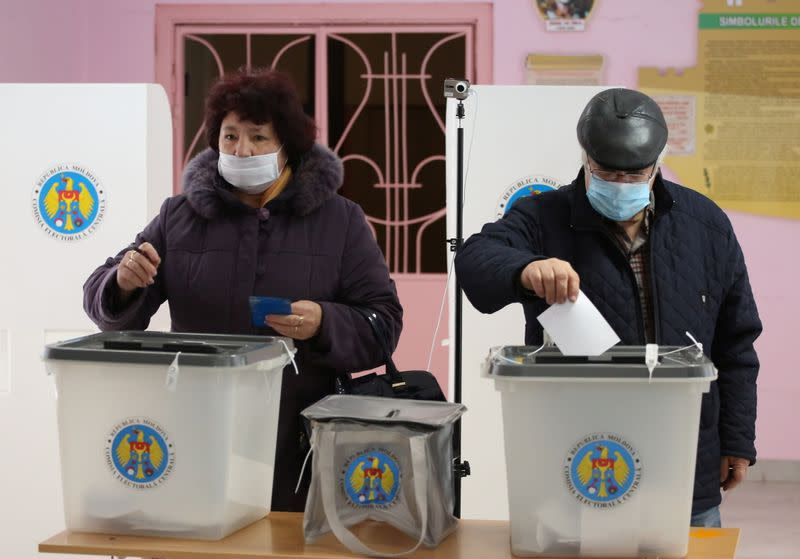 People cast their ballots at a polling station during the second round of a presidential election in Chisinau
