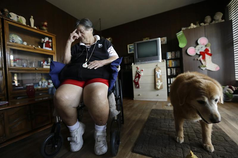 In this Dec. 10, 2013 image, Sherry Scott sits in a wheel chair, alongside her 10-year-old golden retriever Tootie, at her home in San Diego. Scott, who receives dog food for Tootie through the Animeals program, said she would give her lasagne and pork riblets from Meals on Wheels to Tootie if MOW didn't bring dog food for the dog. The pet food program is sponsored by the Helen Woodward Animal Center. (AP Photo/Gregory Bull)
