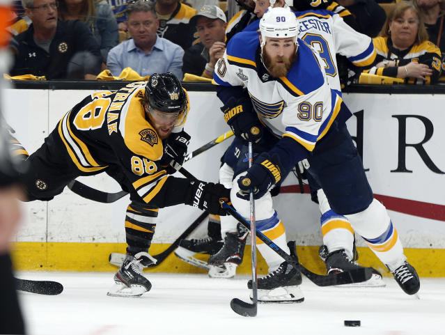FILE - In this June 12, 2019, file photo, St. Louis Blues' Ryan O'Reilly (90) moves the puck away from Boston Bruins' David Pastrnak, left, of the Czech Republic, during the second period in Game 7 of the NHL hockey Stanley Cup Final, in Boston. O'Reilly stockpiled quite the hardware to show off at his Stanley Cup day. On display next to the Cup he helped the St. Louis Blues win were the Conn Smythe Trophy as playoff MVP and the Selke Trophy as the NHL's best defensive forward. (AP Photo/Michael Dwyer)