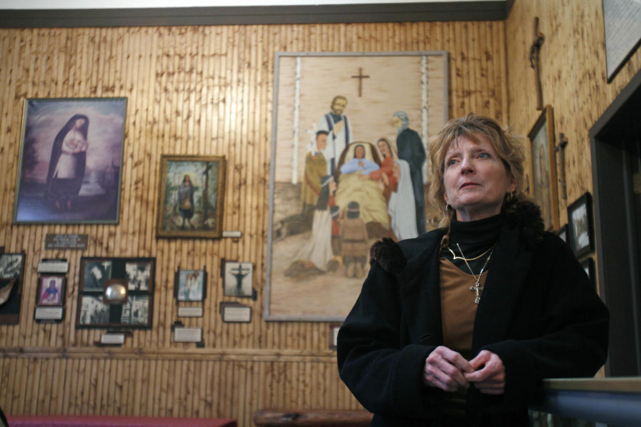 in a Wednesday, Dec. 21, 2011 photo, Beth Lynch, manager of the Martyrs' Shrine in Auriesville, N.Y., poses with items dedicated to the Blessed Kateri Tekakwitha. Tekakwitha, who will be canonized next year, was a Native American baptized in 1676 in the Mohawk Valley. She fled to a mission in Canada after being scorned and threatened in her home village near what is now the village of Fonda. (AP Photo/Mike Groll)