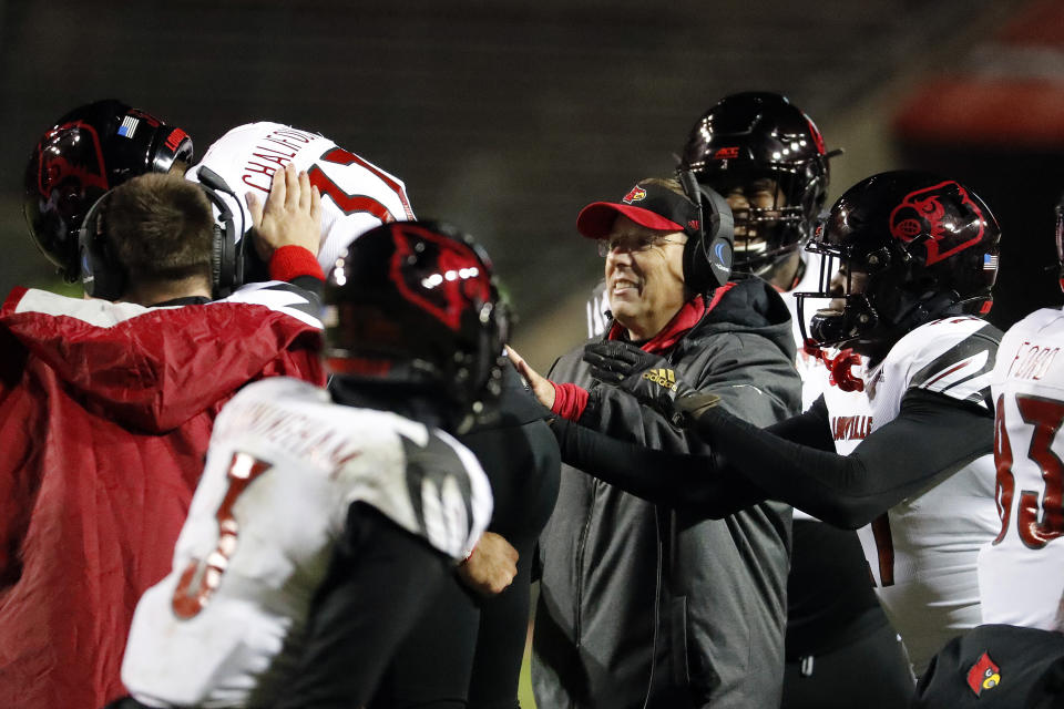 Louisville head coach Scott Satterfield, center, waits to congratulate Ryan Chalifoux (37) on his successful pass for a fake field goal against North Carolina State during the second half of an NCAA college football game in Raleigh, N.C., Saturday, Nov. 16, 2019. (AP Photo/Karl B DeBlaker)