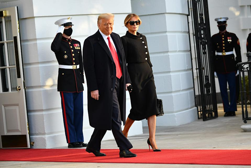 President Donald Trump and first lady Melania make their way to board Marine One before departing from the South Lawn of the White House in Washington on Jan. 20, 2021.