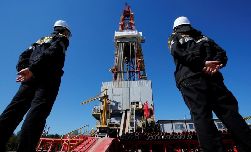 Workers look at a drilling rig of the Rosneft-owned Prirazlomnoye oil field outside Nefteyugansk