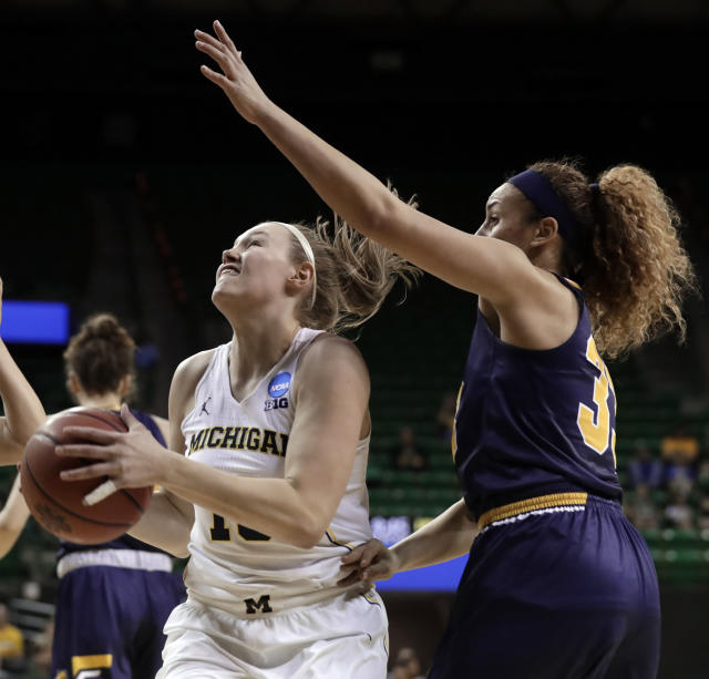 Michigan guard Nicole Munger (10) works for a shot as Northern Colorado guard Kianna Williams (33) defends in the first half of a first-round game at the NCAA women's college basketball tournament in Waco, Texas, Friday, March 16, 2018. (AP Photo/Tony Gutierrez)