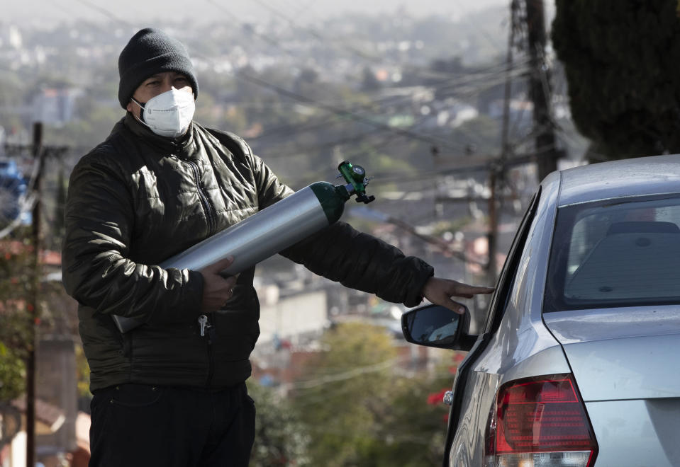Ricardo Ledesma Carrasco gets into his car after refilling a tank of oxygen at a store for his dad who is being treated for COVID-19 at home in Mexico City, Thursday, Dec. 31, 2020. Carrasco's mother also has COVID-19. (AP Photo/Marco Ugarte)