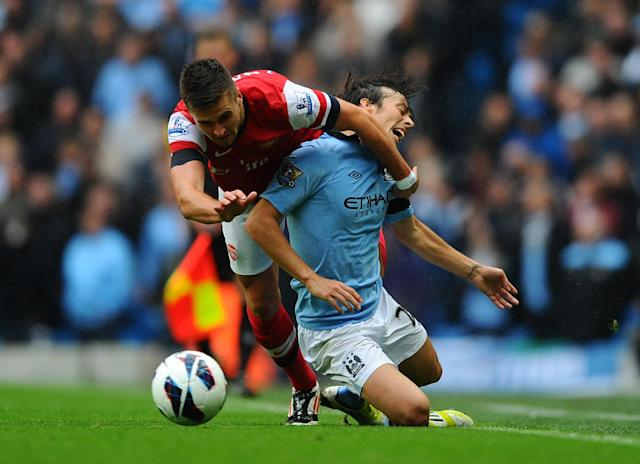 MANCHESTER, ENGLAND - SEPTEMBER 23: Carl Jenkinson of Arsenal clashes with David Silva of Manchester City during the Barclays Premier League match between Manchester City and Arsenal at Etihad Stadium on September 23, 2012 in Manchester, England. (Photo by Laurence Griffiths/Getty Images)