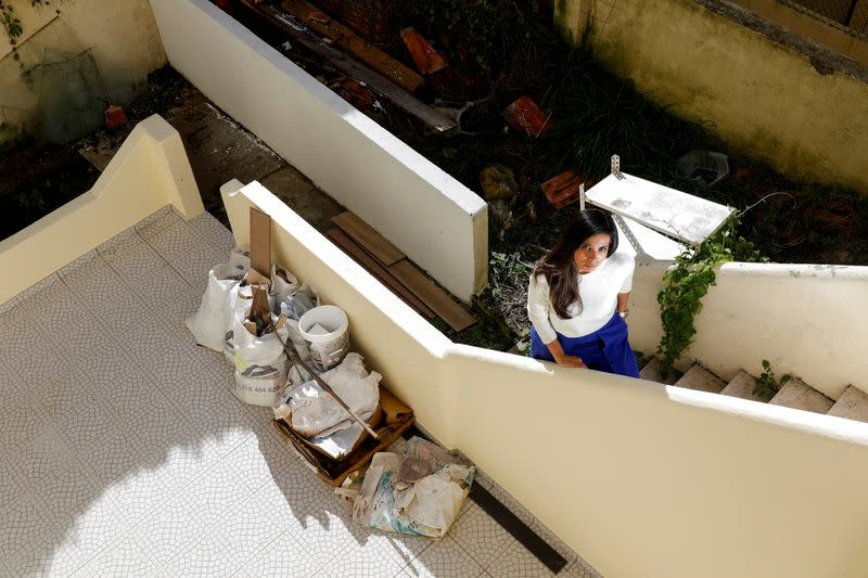Giuliana Miranda poses beside the construction site in front of her apartment building