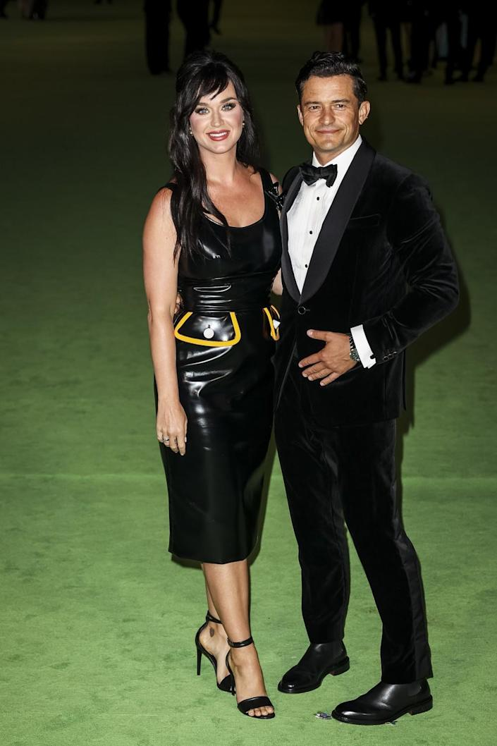 A woman in a black dress and a man in a black tuxedo posing on a green carpet