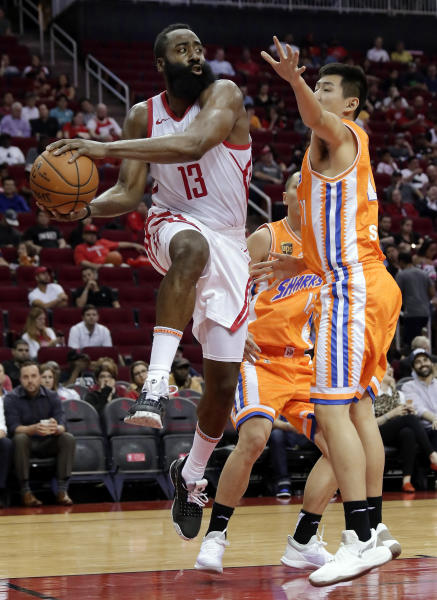 Houston Rockets guard James Harden (13) passes the ball around Shanghai Sharks guard Shi Yuchen (47) during the second half of an exhibition NBA basketball game Tuesday, Oct. 9, 2018, in Houston. (AP Photo/Michael Wyke)
