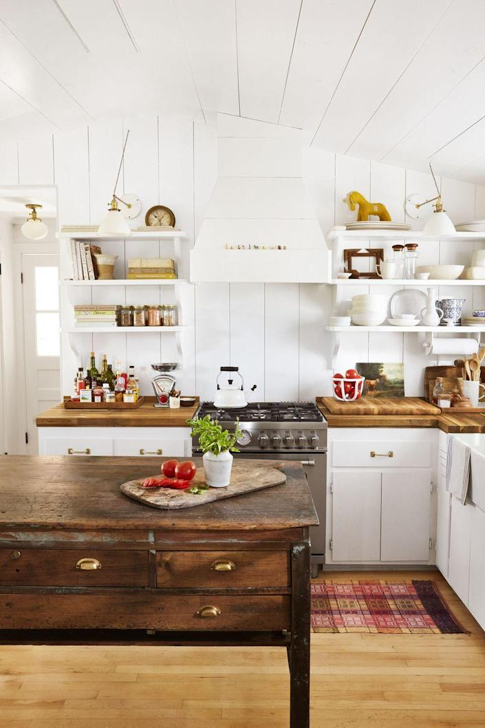 """<p>When it came time to choose the lighting in this all-white kitchen, the homeowners found matching milk glass shades and then went to a lighting store and pieced them all together for """"new"""" sconces. Vertical paneling, shelves, and lower cabinets are all painted a crisp white for a seamless look. An old printing-press work table is now a one-of-a-kind kitchen island.</p>"""