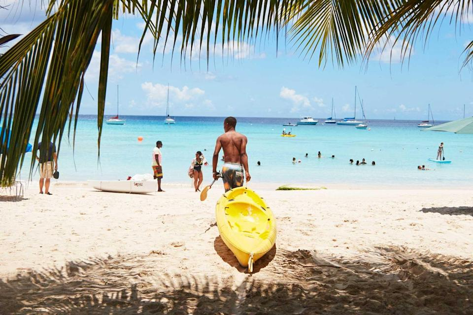A man with a kayak on the beach in Barbados