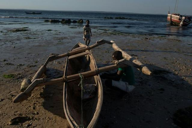 Esheya Talume, 38, repairs his boat. He escaped to Pemba three months ago