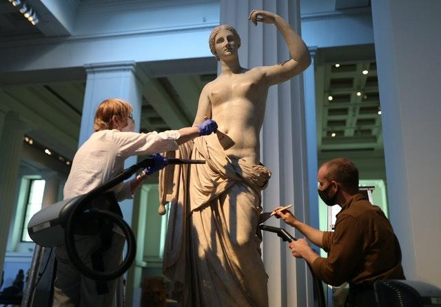 Sovati Smith (left) and Alex Truscott from the collections team dusting the Townley Venus Roman sculpture (1st or 2nd century AD) (Yui Mok/PA)