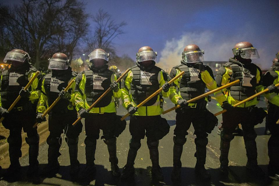 """Tear gas rises from behind a line of Minnesota State Troopers as they block the road from anyone going back towards the Brooklyn Center police station where people protesting the police killing of Daunte Wright in Brooklyn Center, Minnesota, U.S., on April 13, 2021.<span class=""""copyright"""">Christopher Mark Juhn—Anadolu Agency/Getty Images</span>"""